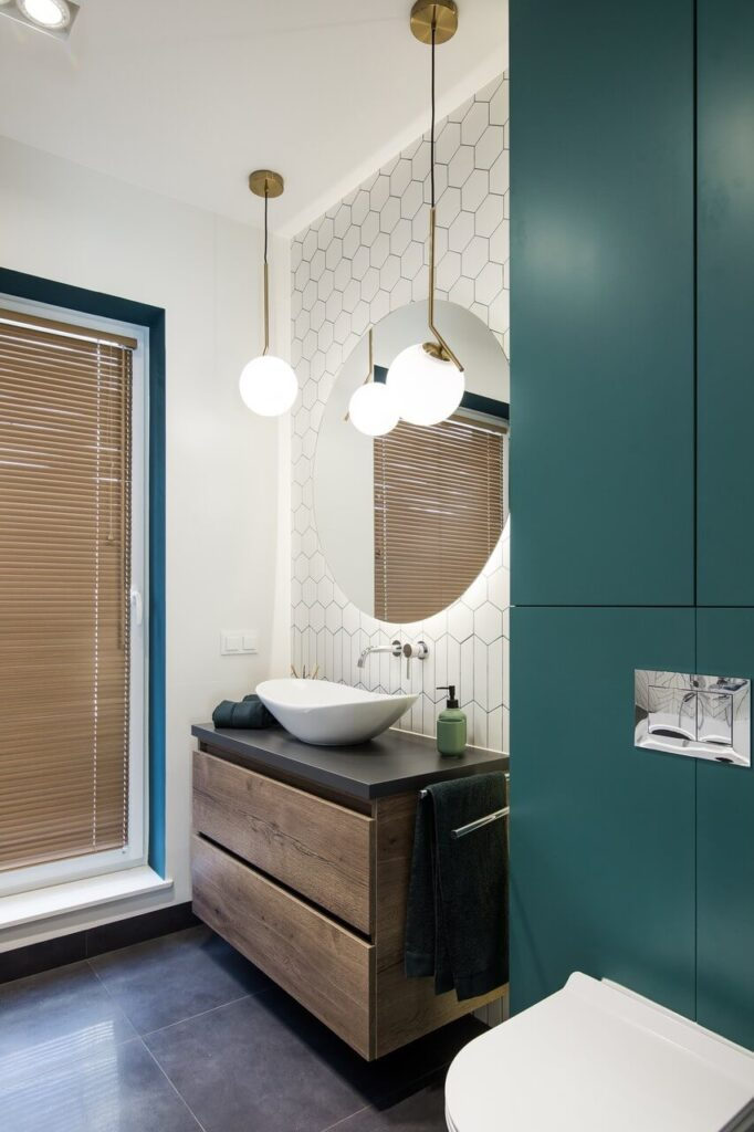 Okrągłe lustro nad umywalką w łazience