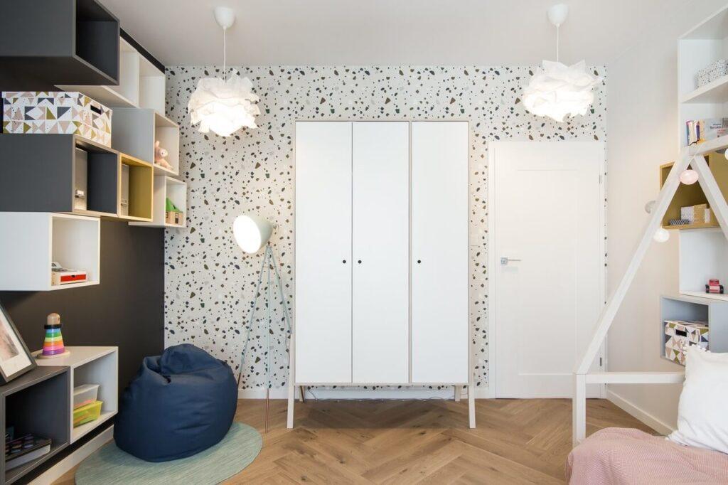 Duża biała szafa na drewnianych nóżkach w pokoju dziecięcym