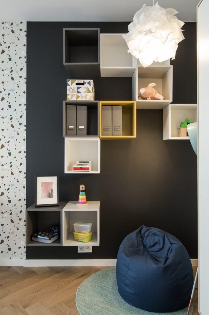Regał w pokoju dziecięcym wiszący na czarnej ścianie
