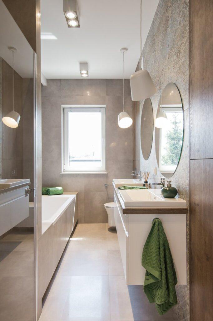 Dwa okrągłe lustra w jasnej łazience